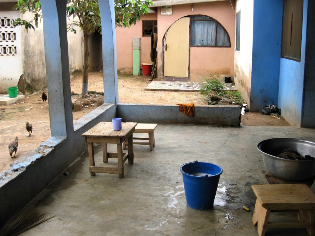 A shared courtyard in Ashaiman, a settlement outside of Accra, showing vessels of water for washing and bathing.